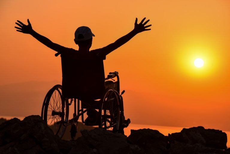 man on a wheelchair watching the sunset